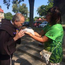 Dovana: pranciškonų vienuolis brolis Bernardas priima duonos kepaliuką iš D.Kunčienės rankų.