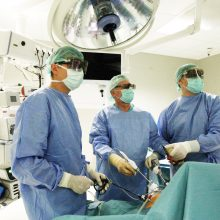 Mūsų fotografas taip pat pastebėjo, kad operacijos trimatėje erdvėje skiriasi nuo įprastų, nes operacinė skendi tamsoje, o užsidėję specialius akinius chirurgai susmeigę akis žiūri į vaizdo monitorių.